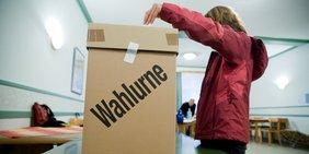 Frau wirft Wahlzettel in Wahlurne
